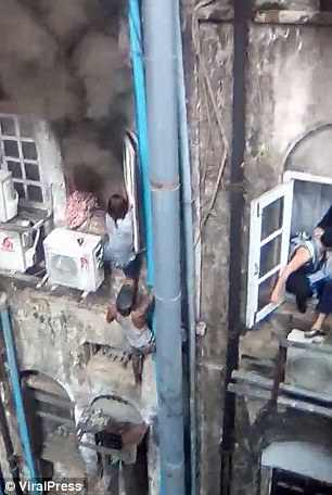 Pyae climbs up the pipe to save the terrified woman. Credit: Viral Press