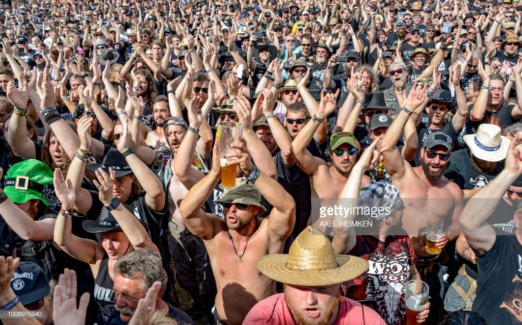 Visitors of the Wacken Open Air heavy metal music festival cheer during the performance of the local fire brigades band on August 1, 2018 in Wacken, northwestern Germany. (Photo by Axel Heimken / dpa / AFP) / Germany OUT (Photo credit should read AXEL HEIMKEN/AFP/Getty Images)