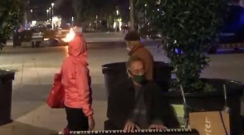 Pianist calmly plays while all hell breaks loose in anti-lockdown riots behind him