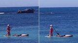 Sheila paddleboards bloke around while he snorkels